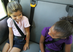 Two young girls sit on the school bus buckled up in SafeGuard seat belts.
