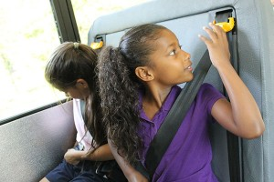 A young girl buckles up in her SafeGuard lap-shoulder belt.
