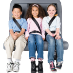 3 young students are buckled up in their SafeGuard seat belts on a single school bus seat.